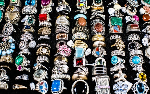 Dozens of vintage rings on black velvet display board